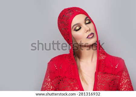 Alluring sexy young woman in red knitted jacket with bright make up and beautiful slim body standing with closed eyes on grey wall background copy space, horizontal picture - stock photo