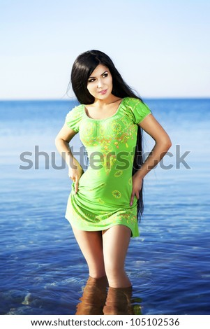 Alluring slim girl resting at beach in water in hot summer day- happy smiling woman enjoying sun. Romantic woman relaxing at vacation holidays near sea. Beautiful sexy bikini pinup model at resort - stock photo
