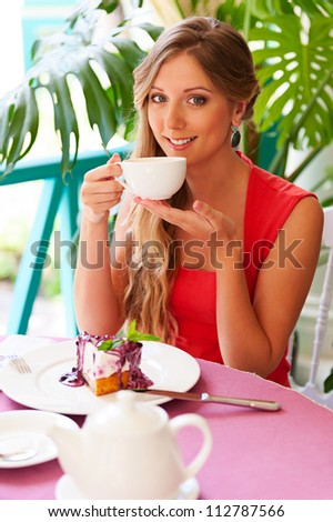 alluring smiley woman drinking tea in the cafe - stock photo