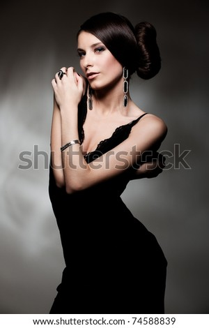 alluring woman in black dress posing over dark background