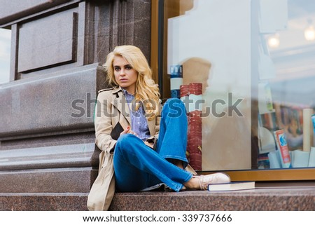 Alluring woman posing while sitting with textbook on store sill in autumn day, charming female enjoying her recreation time during spring weekend, pretty blonde girl relaxing after strolling outdoors  - stock photo