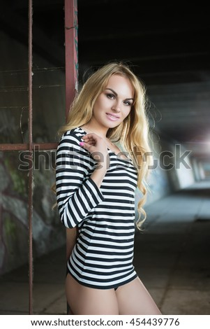 Alluring young blonde in striped blouse posing near iron fence - stock photo
