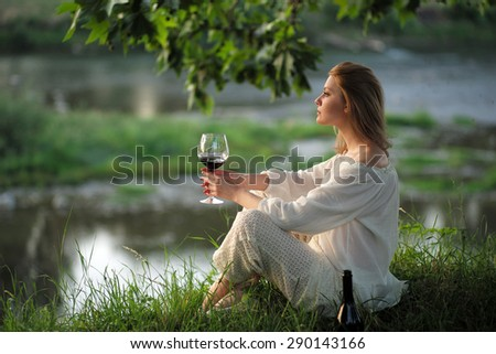 Alluring young lady in white clothes sitting on river bank in calm drinking red wine on natural sunset background, horizontal picture - stock photo