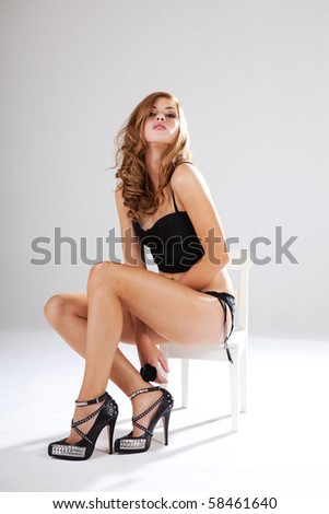 Alluring young woman in black lingerie sits in a white chair while looking into the camera. Vertical shot. - stock photo