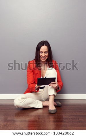 alluring young woman sitting on the floor and using tablet pc - stock photo