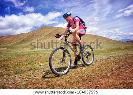 "ALMATY, KAZAKHSTAN - APRIL 30: I.Popov (N3) in action at Adventure mountain bike cross-country marathon in mountains ""Jeyran Trophy 2012"" April 30, 2012 in Almaty, Kazakhstan. - stock photo"
