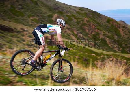 "ALMATY, KAZAKHSTAN - APRIL 30: K.Rachyk (N25) in action at Adventure mountain bike cross-country marathon in mountains ""Jeyran Trophy 2012"" April 30, 2012 in Almaty, Kazakhstan. - stock photo"