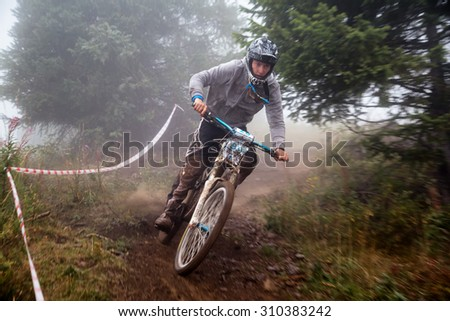 ALMATY, KAZAKHSTAN - AUGUST 22, 2015: A.Zubenko (N99) in action at Mountain Bike sports event DOWNHILL EXTREME WEEKEND.  - stock photo