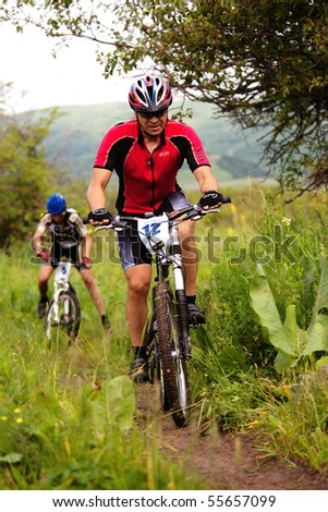 "ALMATY, KAZAKHSTAN - JUNE 20: I.Baranov (N12) in action at Adventure mountain bike cross-country competition ""Ak Bulak 2010"" June 20, 2010 in Almaty, Kazakhstan - stock photo"