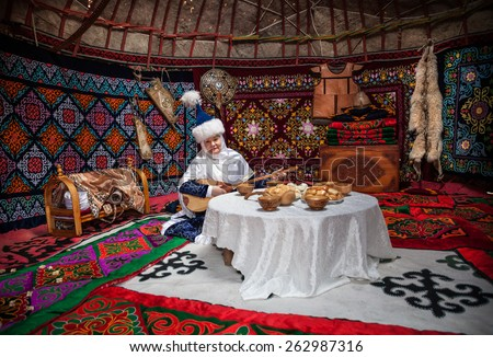 ALMATY, KAZAKHSTAN - MARCH 22, 2015: Woman in national Kazakh costume with dombra music instrument near the table with national food in Yurt nomadic house at Nauryz celebration - stock photo