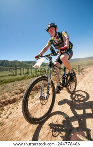 "ALMATY, KAZAKHSTAN - MAY 05, 2013: A.Litvinov (N30) in action at Adventure mountain bike cross-country competition in mountains ""Jeyran Trophy 2013""  - stock photo"