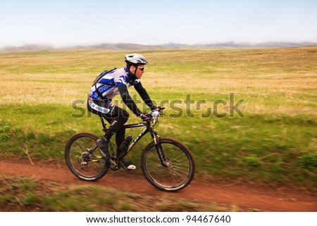 """ALMATY, KAZAKHSTAN - MAY 2: M.Kolbasov (N24) and others in action at Adventure mountain bike cross-country marathon in mountains """"Jeyran Trophy 2010"""" May 2, 2010 in Almaty, Kazakhstan. - stock photo"""
