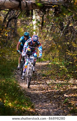 ALMATY, KAZAKHSTAN - OCTOBER 16: I. Feodoseev (No. 87) in action at cross-country mountain bike 'Apple race' on October 16, 2011 in Almaty, Kazakhstan. - stock photo
