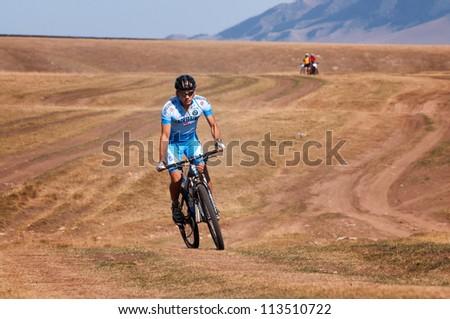 "ALMATY, KAZAKHSTAN - SEPTEMBER 09: An unidentified rider in action at Adventure mountain bike cross-country marathon ""Marathon Bartogay-Assy-Batan 2012"" on September 09, 2012 in Almaty, Kazakhstan. - stock photo"