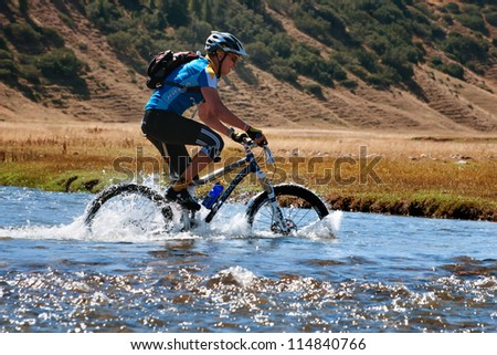 "ALMATY, KAZAKHSTAN - SEPTEMBER 09: M.Sotnikov (N5) in action at Adventure mountain bike cross-country marathon ""Marathon Bartogay-Assy-Batan 2012"" on September 09, 2012 in Almaty, Kazakhstan. - stock photo"