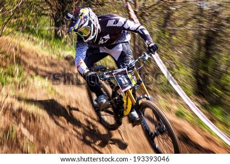 ALMATY, KAZAKSTAN - APRIL 27, 2014: Unknown rider in action at Mountain Bike sports event Downhill Koktybe.  - stock photo