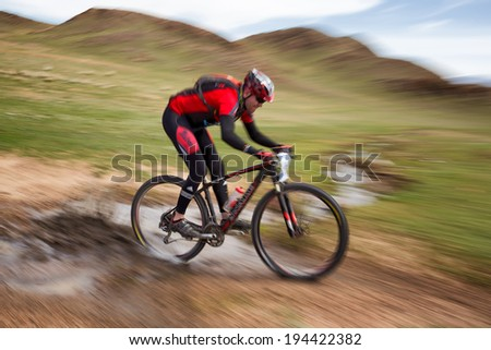 "ALMATY, KAZAKSTAN - MAY 01, 2014: A.Kovalgonov (N14) in action at Adventure mountain bike cross-country marathon in mountains ""Jeyran Trophy 2014""  - stock photo"