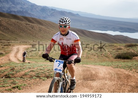 "ALMATY, KAZAKSTAN - MAY 02, 2014: A.Pak (N7) in action at Adventure mountain bike cross-country marathon in mountains ""Jeyran Trophy 2014""  - stock photo"