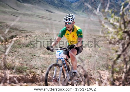 "ALMATY, KAZAKSTAN - MAY 01, 2014: A.Pak (N7) in action at Adventure mountain bike cross-country marathon in mountains ""Jeyran Trophy 2014""  - stock photo"