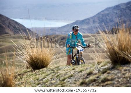 "ALMATY, KAZAKSTAN - MAY 03, 2014: R.Kuznetcov (N9) in action at Adventure mountain bike cross-country marathon in mountains ""Jeyran Trophy 2014""  - stock photo"