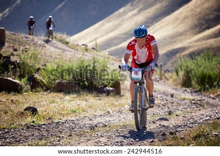 "ALMATY, KAZAKSTAN - SEP 05, 2010: E.Kazantcev (N6) in action at Adventure mountain bike cross-country competition in mountains ""Bartogay Marathon 2010""  - stock photo"