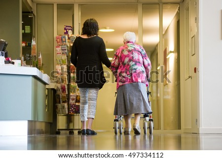ALMELO, THE NETHERLANDS - JUNE 15, 2016: A woman is assisting an elderly woman with a rollator in an elderly home.