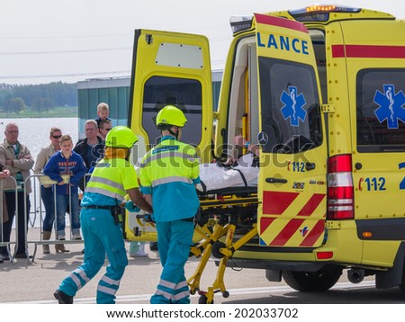 ALMERE, NETHERLANDS - 12 APRIL 2014: Medical services at work in an enacted emergency scene during the first National Security Day held in the city of Almere - stock photo