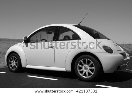 Almere Poort, Flevoland, The Netherlands - June 6, 2015: Volkswagen Beetle parked in a public parking lot in front of a sand dune and under a clear blue sky. Nobody in vehicle. - stock photo