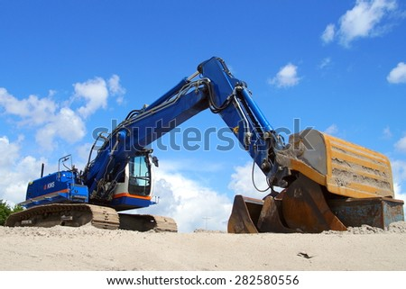 Almere, The Netherlands - May 30, 2015: Crawler Excavator Crane (earth mover) sits at rest on a sandy on a Dutch construction site