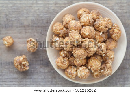 Almond and caramal popcorn on wood background