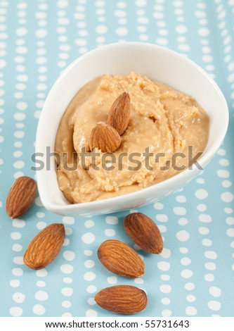 Almond Butter in White Bowl with Almonds Around - stock photo