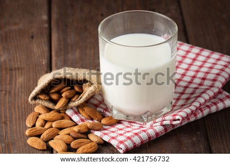 Almond milk in a glass with almond nuts on a wooden table. Healthy food concept. - stock photo