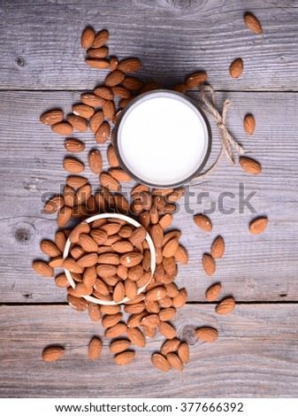 Almond milk in glass with almonds in bowl, on wooden background - stock photo