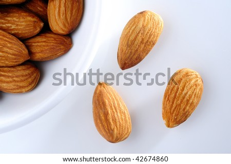 almond nut in white cup and almond on white background. top eye view.