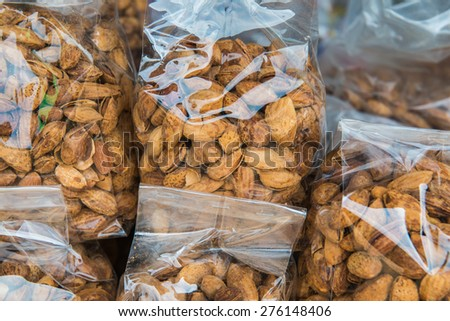 Almond nuts in plastic bag on sale stand, Thailand. - stock photo