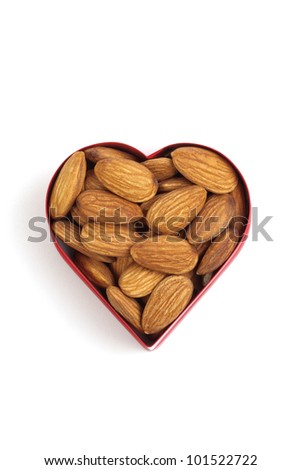 Almond nuts inside heart shaped container, isolated on white background, copy space
