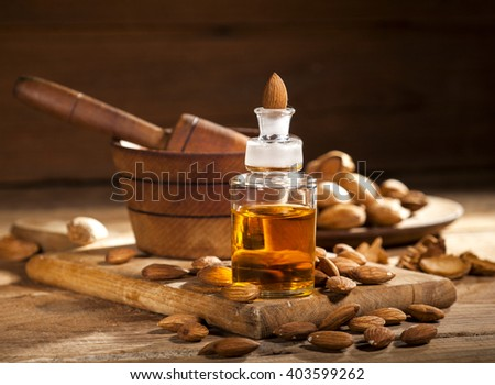 Almond oil and nuts on an old wooden background, selective focus - stock photo
