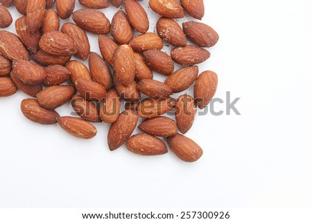 almond seeds with salt are pouring on white background - stock photo