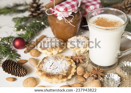 Almond tarts, cup of milk and the Christmas decoration on a white wooden background
