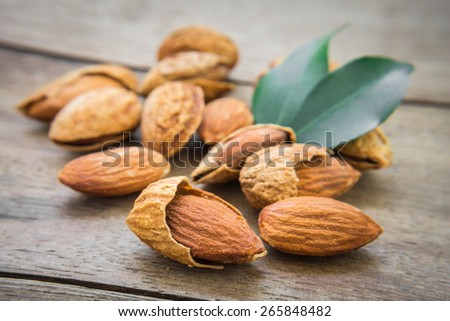 Almond with leaves on wooden table  - stock photo