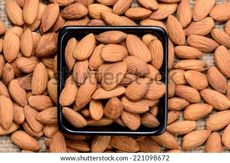 almonds - a ceramic bowl on grained background