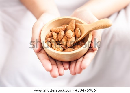 almonds, almonds in a wooden spoon and bowl on hand