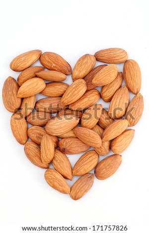 Almonds arranged in heart shape on white background - stock photo