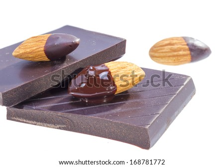 Almonds dipped in chocolate over sweet bar isolated on white background. - stock photo