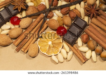 Almonds, hazelnuts and spices with chocolate as background - stock photo