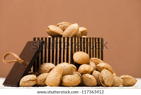 Almonds in a wooden box on a brown background - stock photo