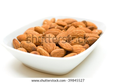Almonds in bowl over white background - stock photo