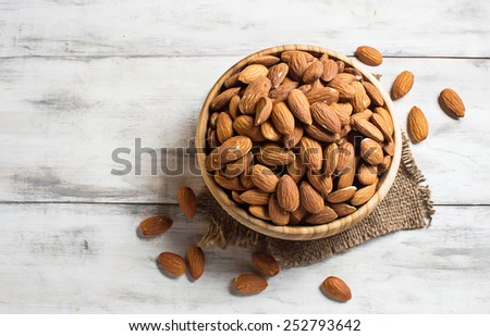Almonds in brown bowl on wooden background - stock photo