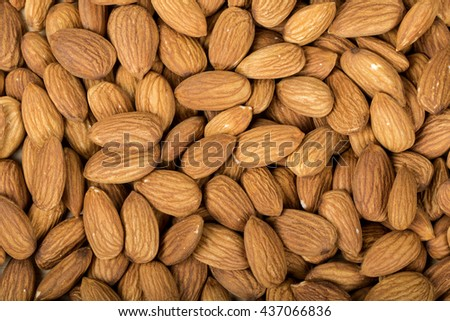 Almonds in brown bowl on wooden background, group of almonds, sackcloth - stock photo