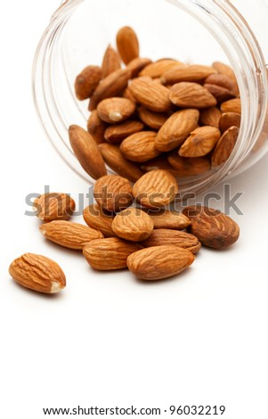 Almonds in the plastic jar on white - stock photo